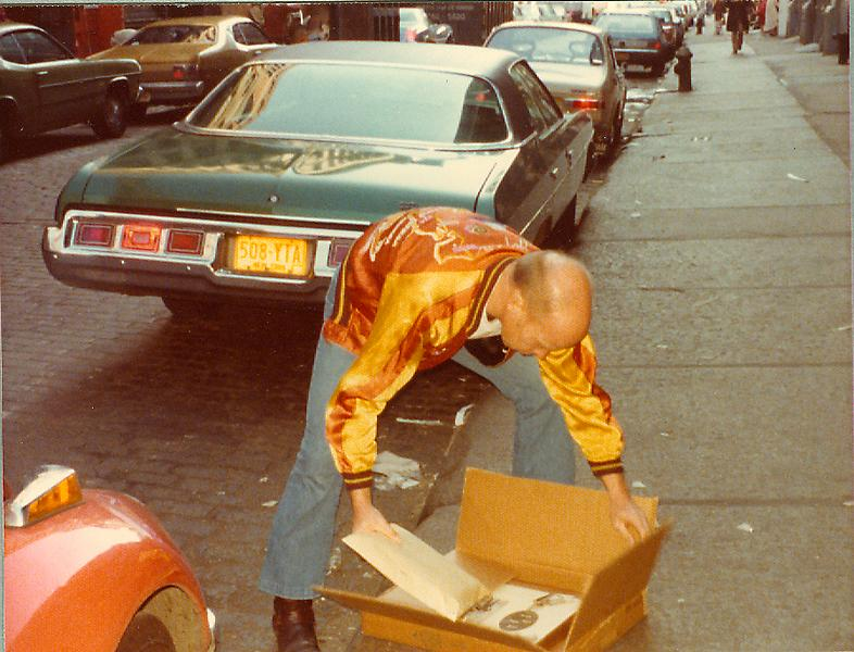 Ray Johnson unloading a box of moticos by a car, April 1976