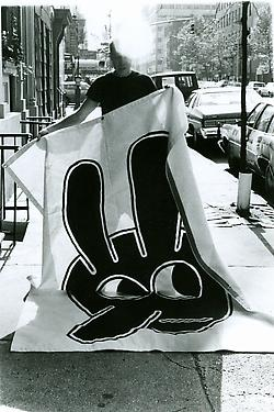 Johnson holding a banner of a bunny head, preparing for a performance, 1991
